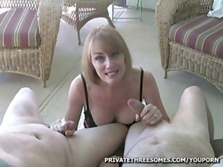 horny blond woman is giving two guys and handjob