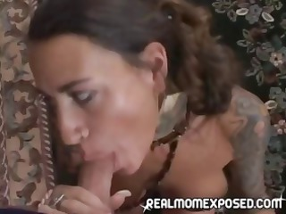 ethnic milf with heavily tattooed arms giving an